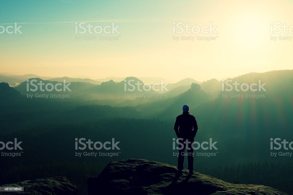 Slim tourist on rock edge over misty and foggy valley stock photo