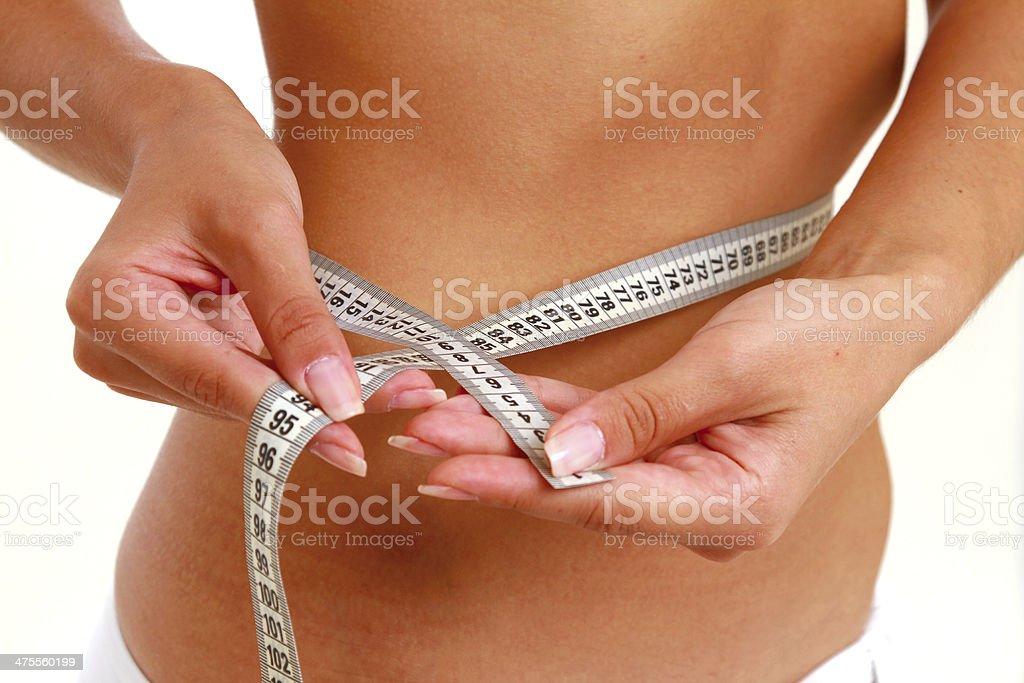 Slim waist with a tape measure around it stock photo