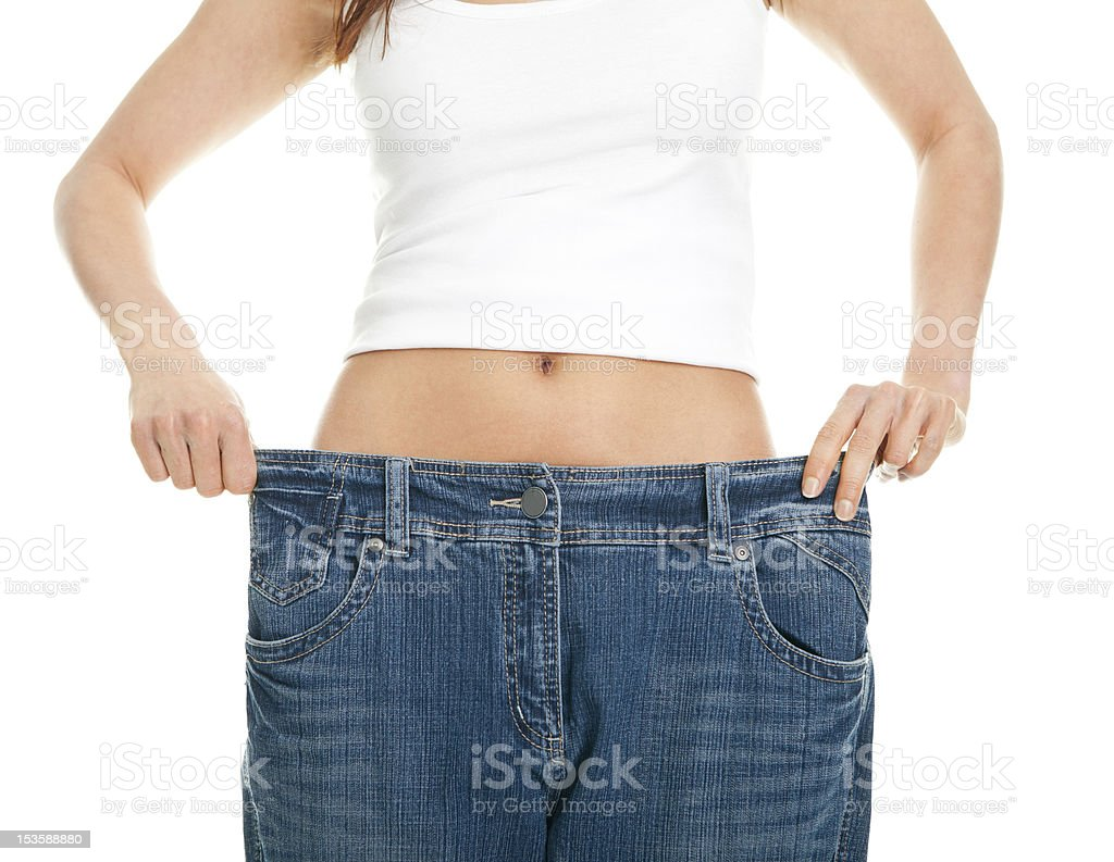 Slim woman pulling oversized jeans royalty-free stock photo