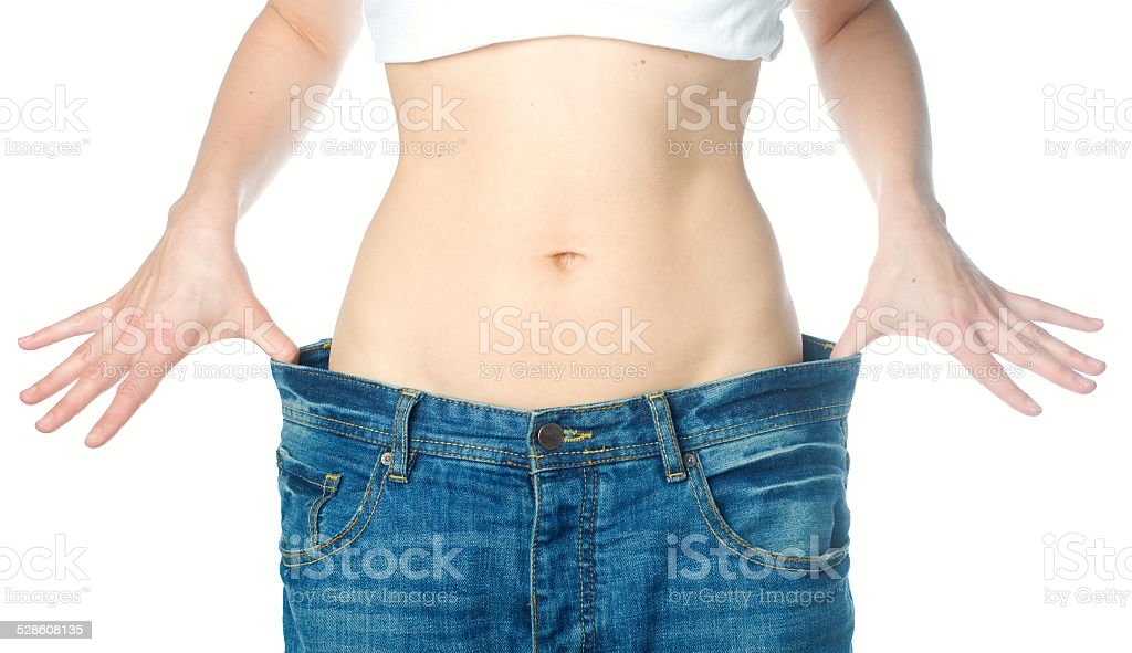 Slim woman shows her weight loss stock photo