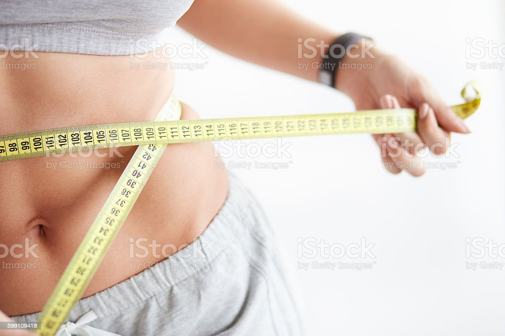 Slim young woman measuring her thin waist with a tape stock photo