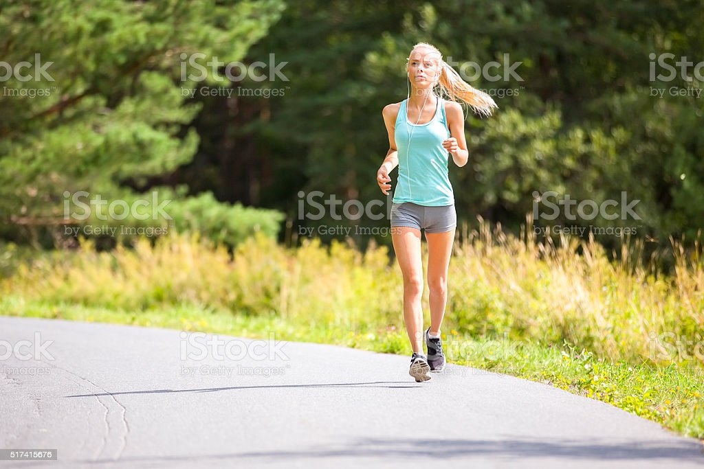 Slim young woman running on a road in the forest stock photo