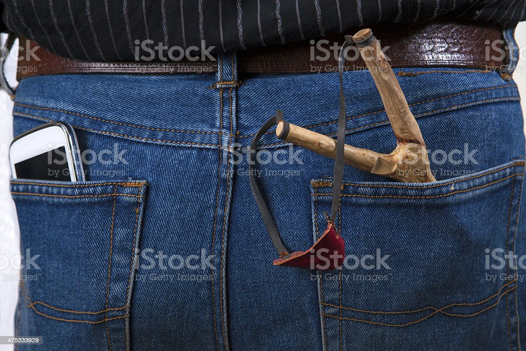 Slingshot and a cell phone in jeans, royalty-free stock photo