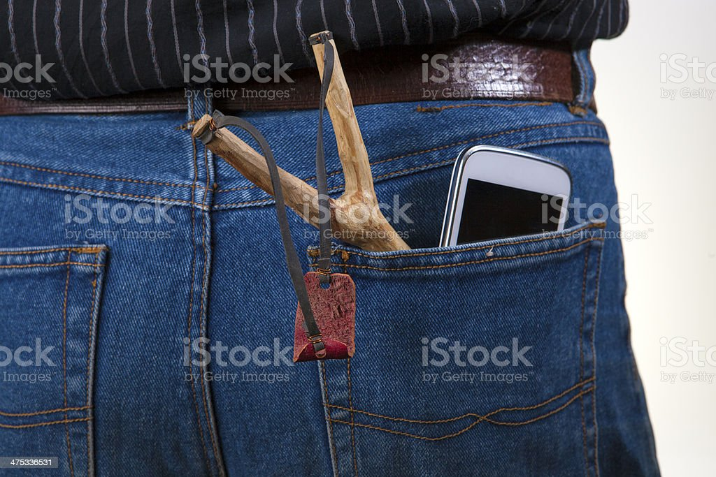 Slingshot and a cell phone in jeans, stock photo