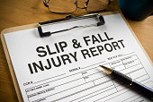 Slip and Fall Injury Report with clipboard on a desk