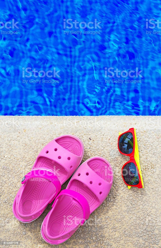 Slippers and sunglasses near the pool. Space for text. stock photo