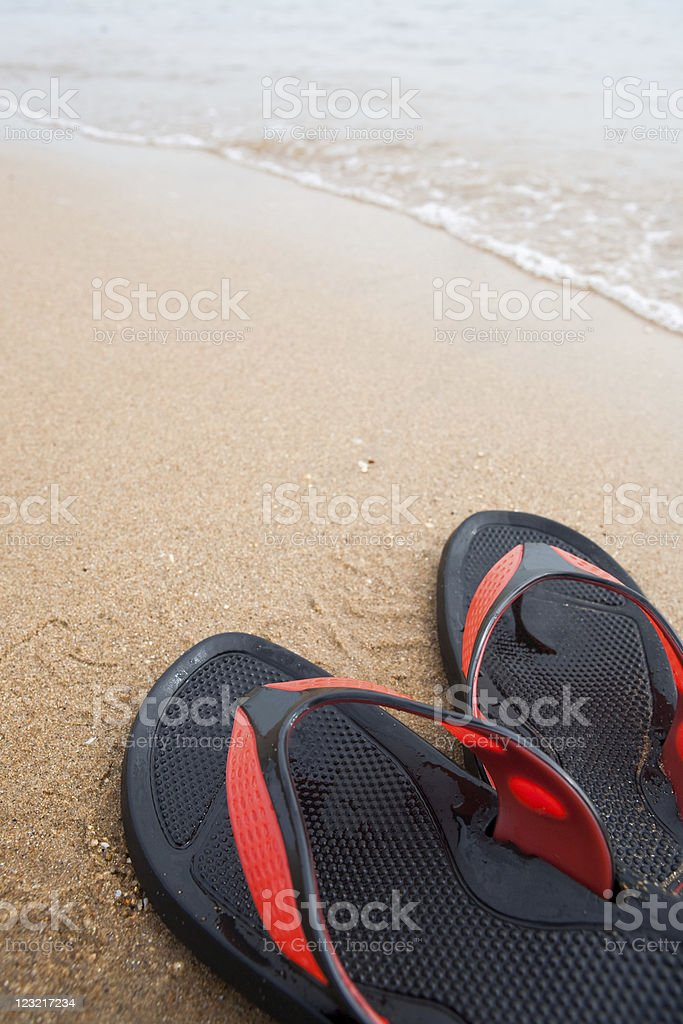 Slippers in the waves royalty-free stock photo