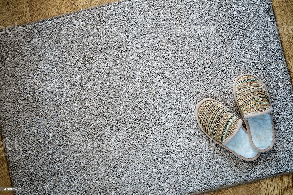 Slippers on the mat, top view with space for text stock photo