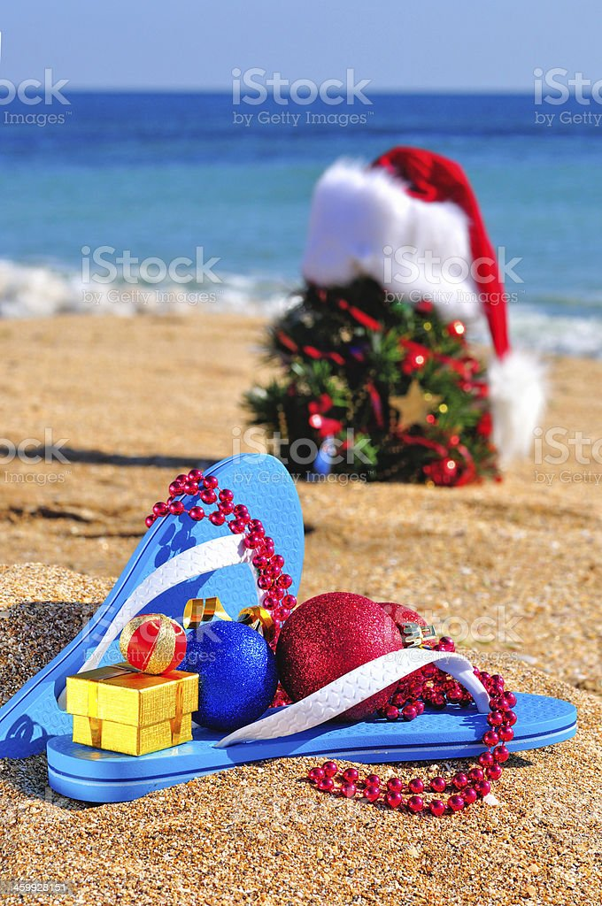 Slippers, Santa Claus hat, new year tree on the seashore stock photo