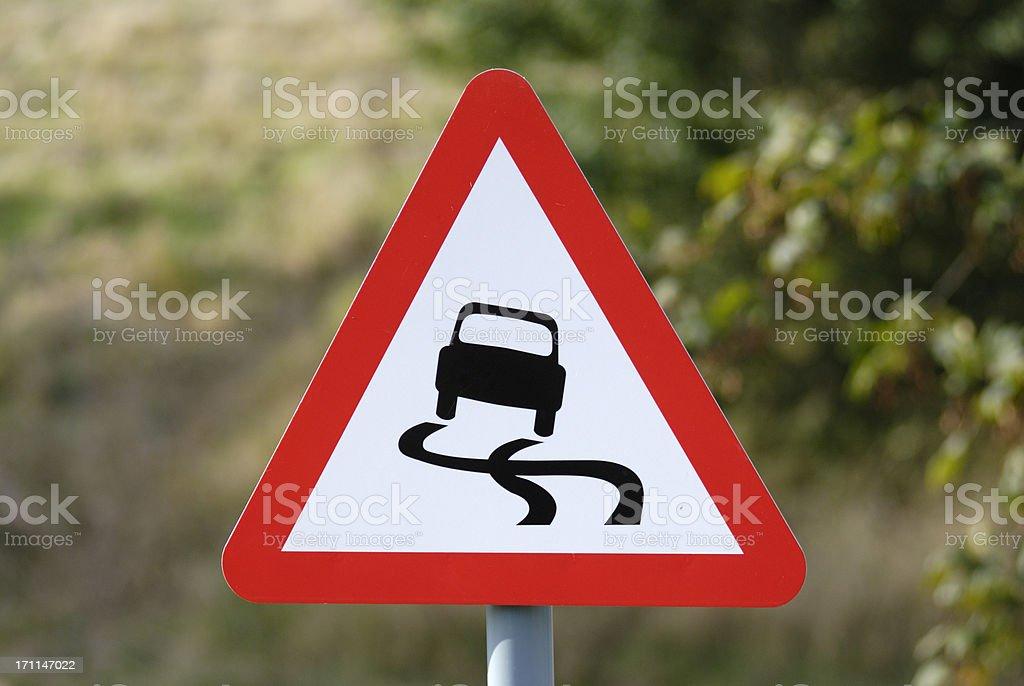 Slippery road warning sign showing hazard ahead stock photo