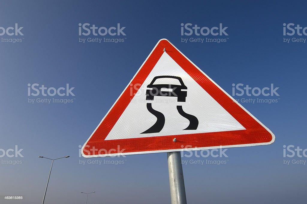 Slippery road warning sign showing hazard ahead. stock photo