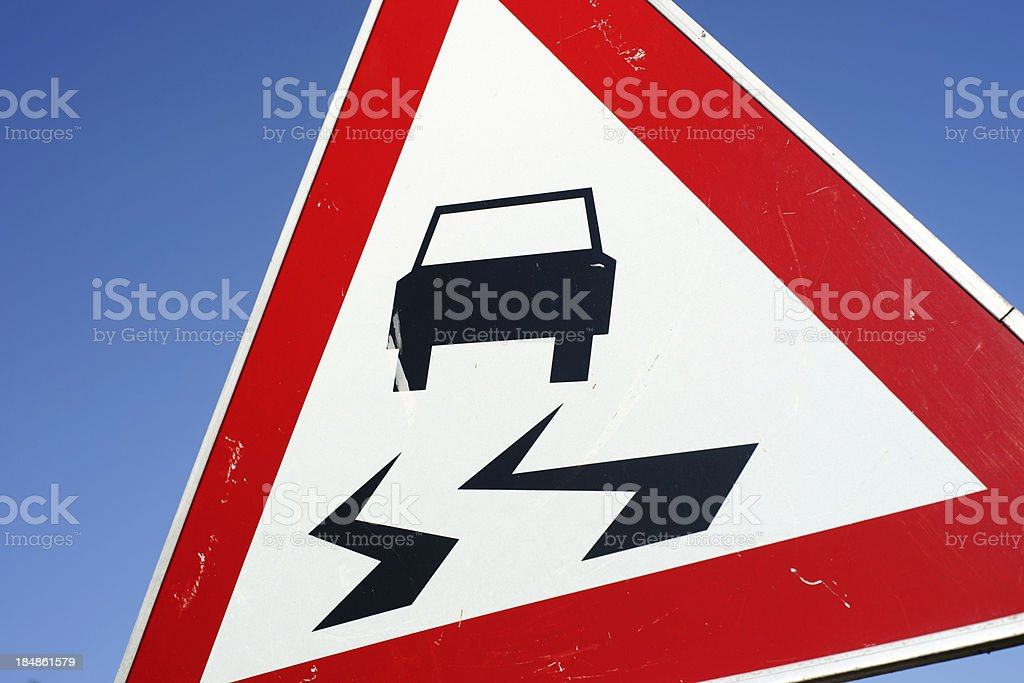 Slippery road warning traffic sign - close up royalty-free stock photo