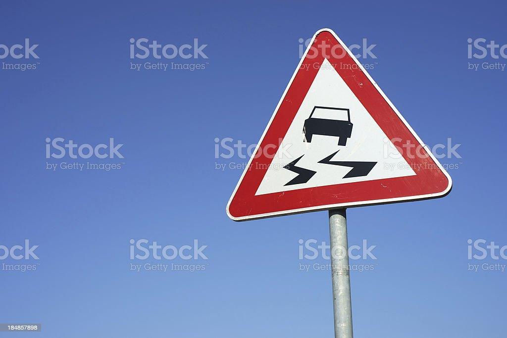 Slippery road warning traffic sign stock photo