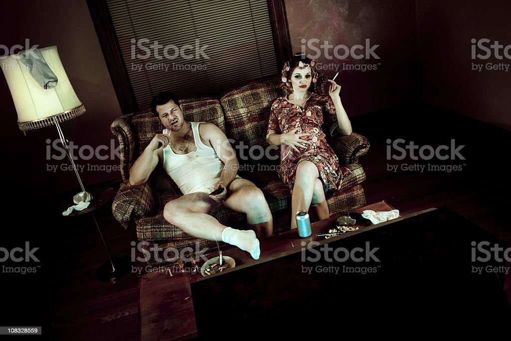 Slob couple watching television with pregnant woman smoking stock photo