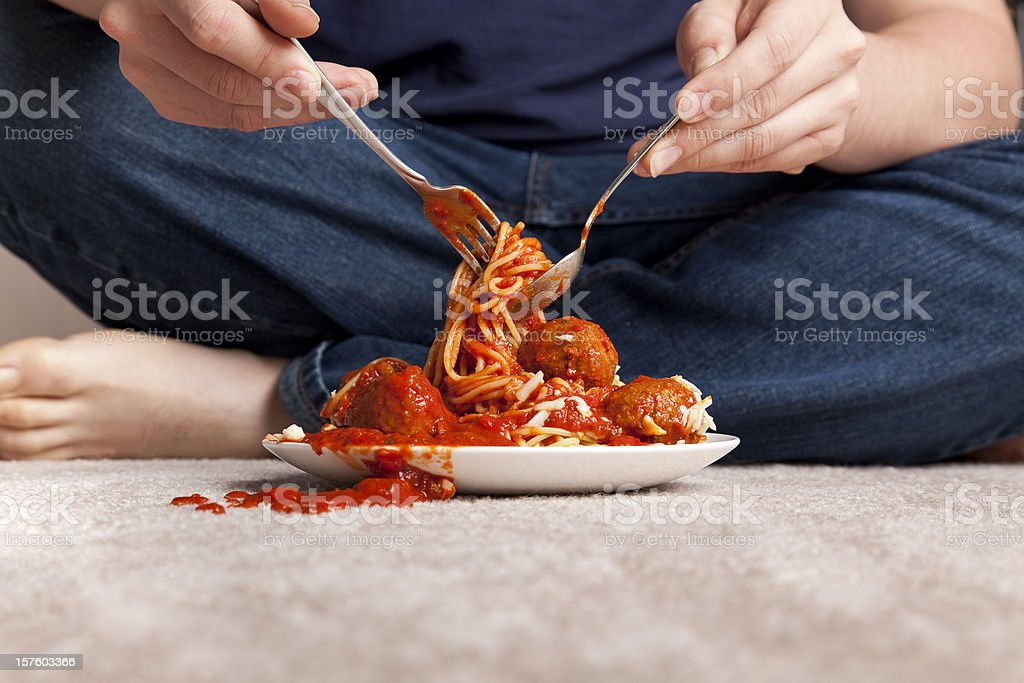 Slob eat spaghetti and meatballs sitting on a carpeted floor stock photo