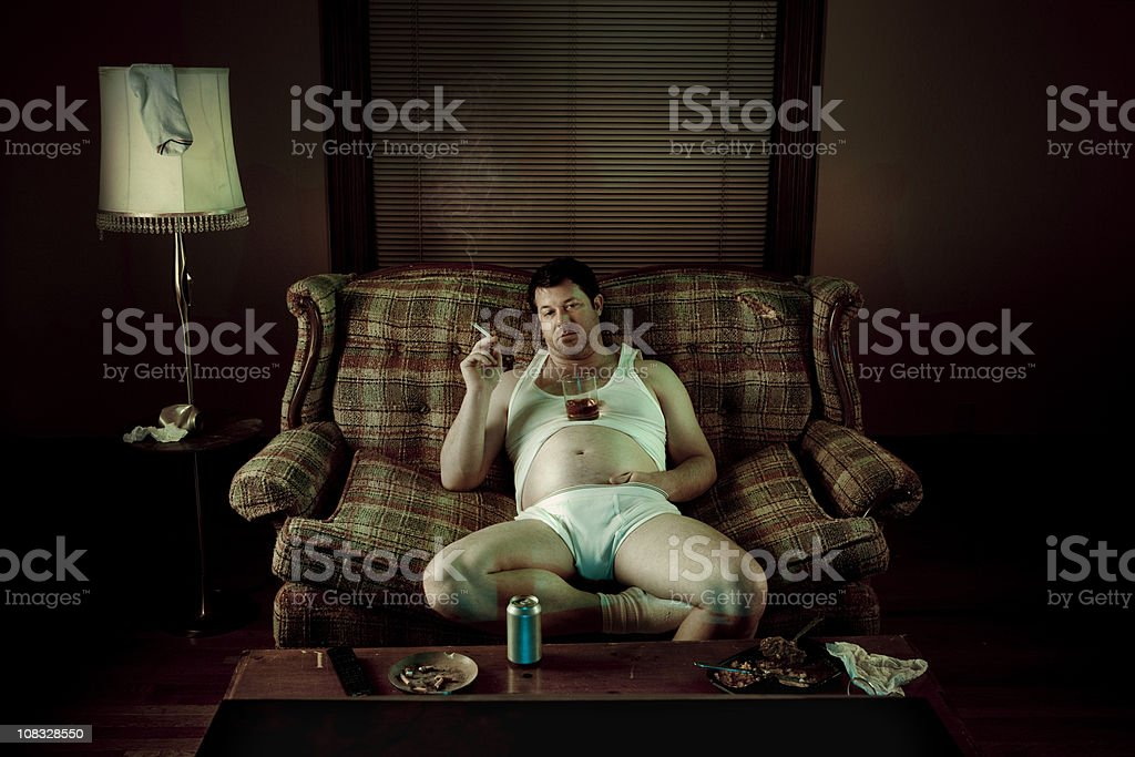Slob Man watching television while smoking in underwear stock photo