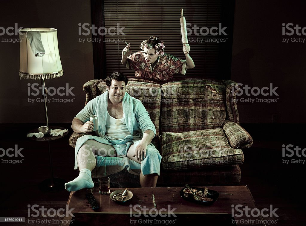 Slob Man watching television while smoking woman waves rolling pin royalty-free stock photo
