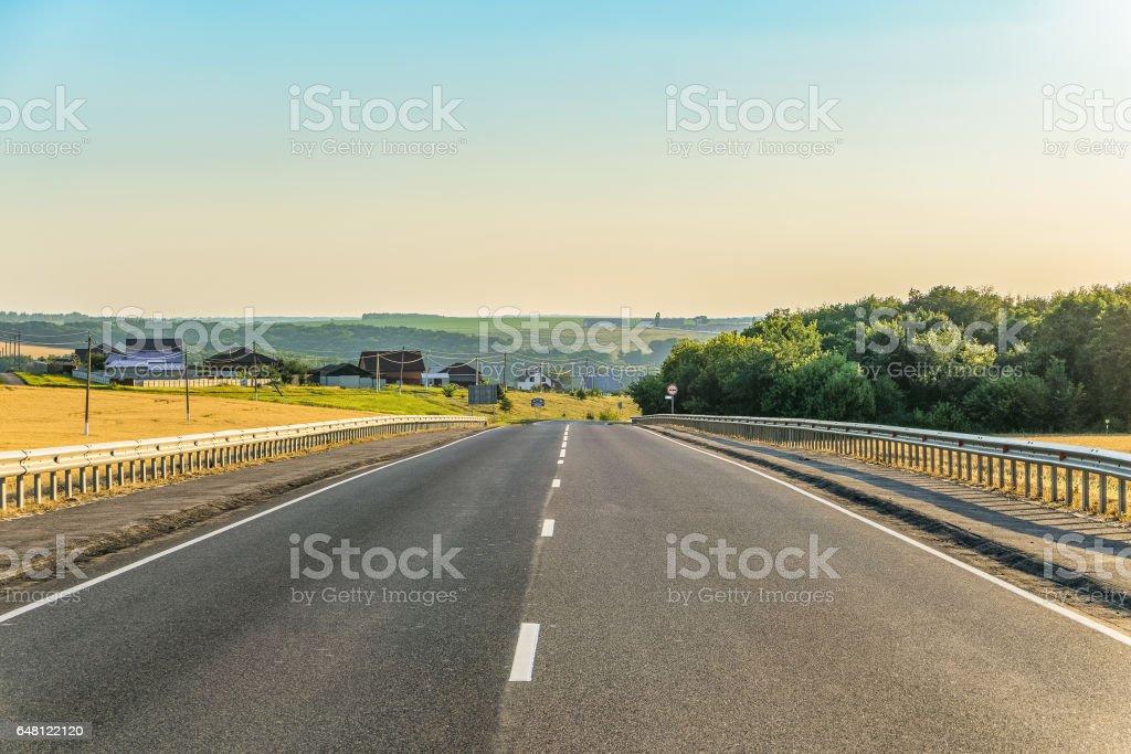 Slope rural asphalt road with marking and guard rails. Belgorod region, Russia. stock photo