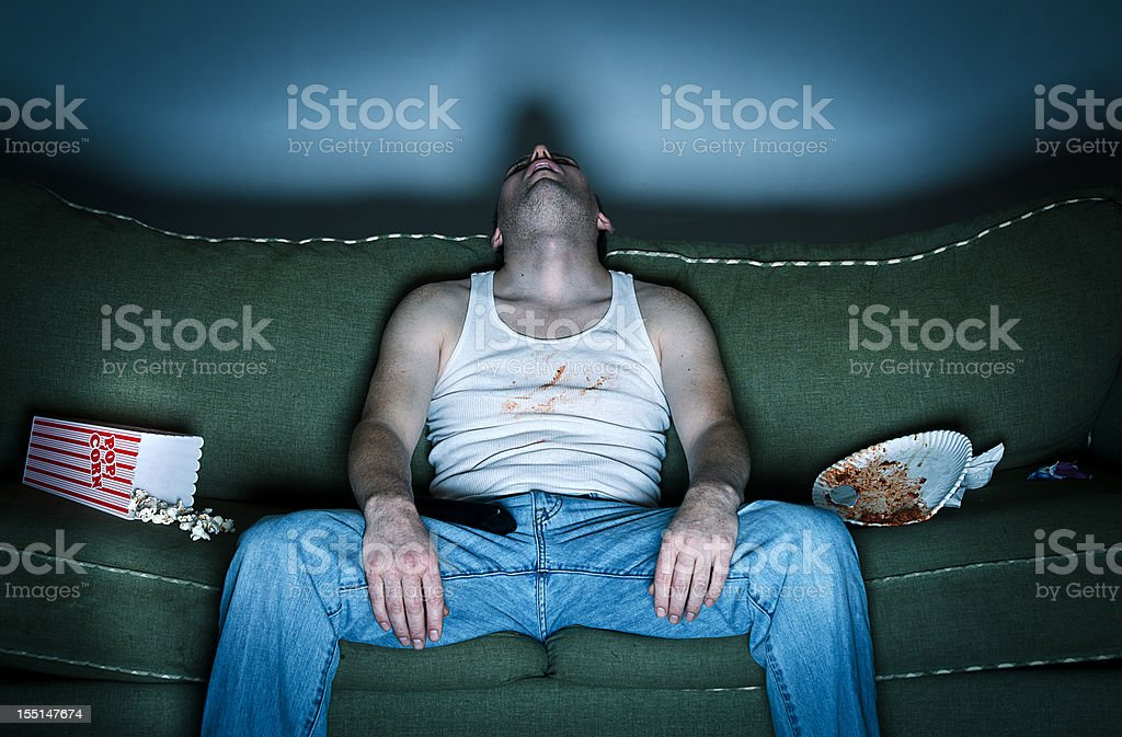 Sloppy man asleep on the couch stock photo