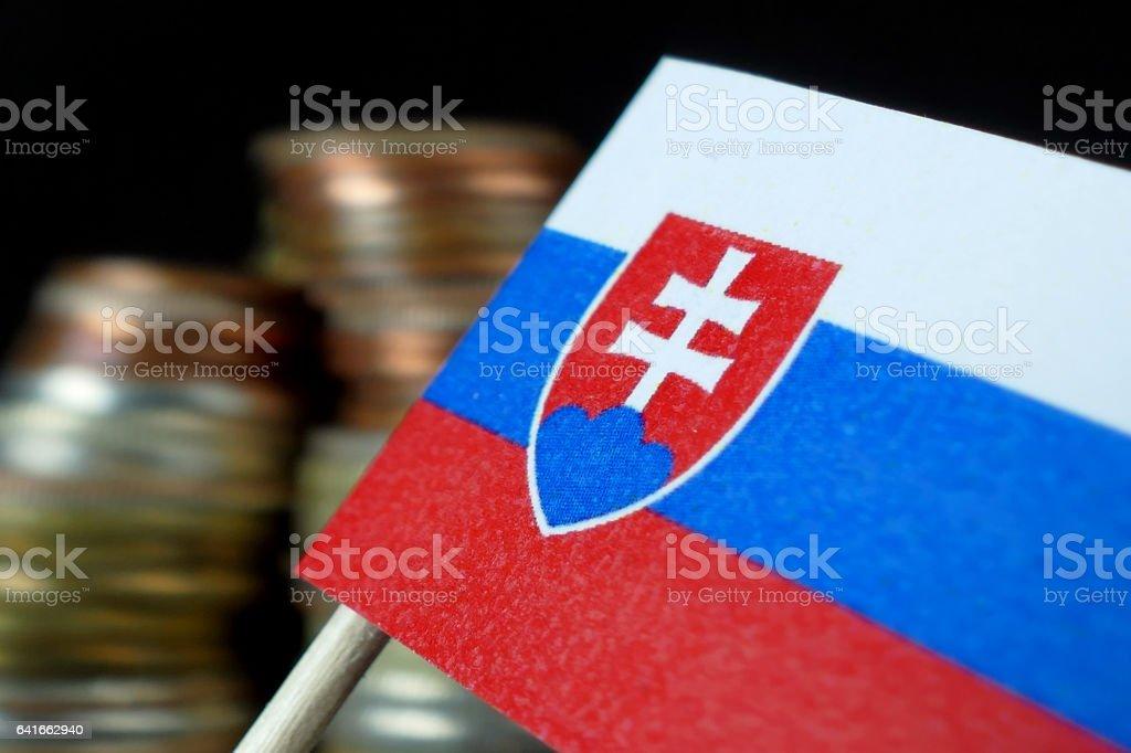 Slovakia flag waving with stack of money coins macro stock photo