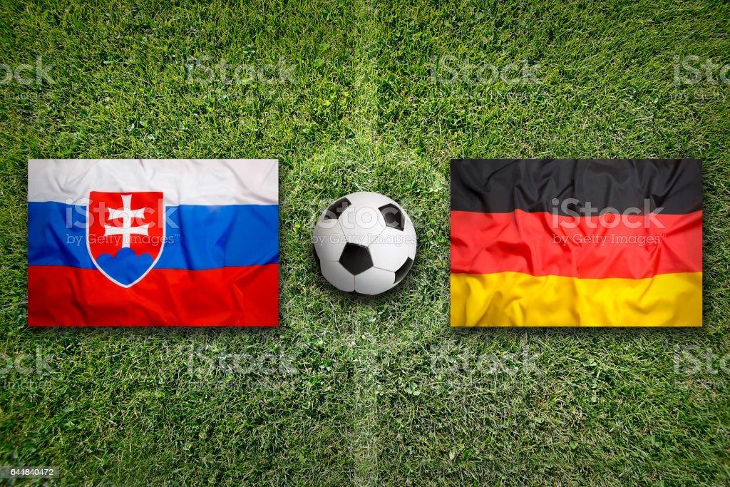 Slovakia vs. Germany flags on soccer field stock photo