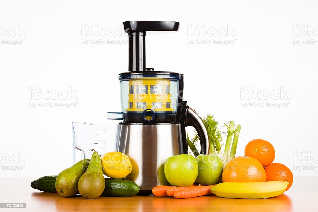 slow juicer with fresh fruit and vegetables on a table stock photo