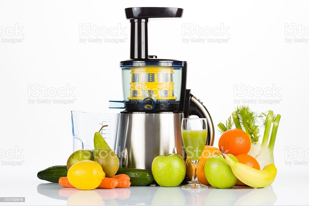 slow juicer with fruit, vegetables and a glass of juice stock photo
