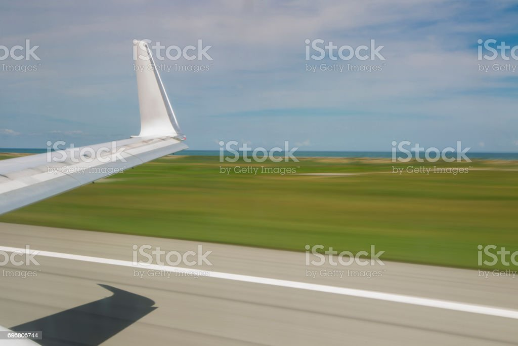 Slow shutter view of plane wing at takeoff stock photo