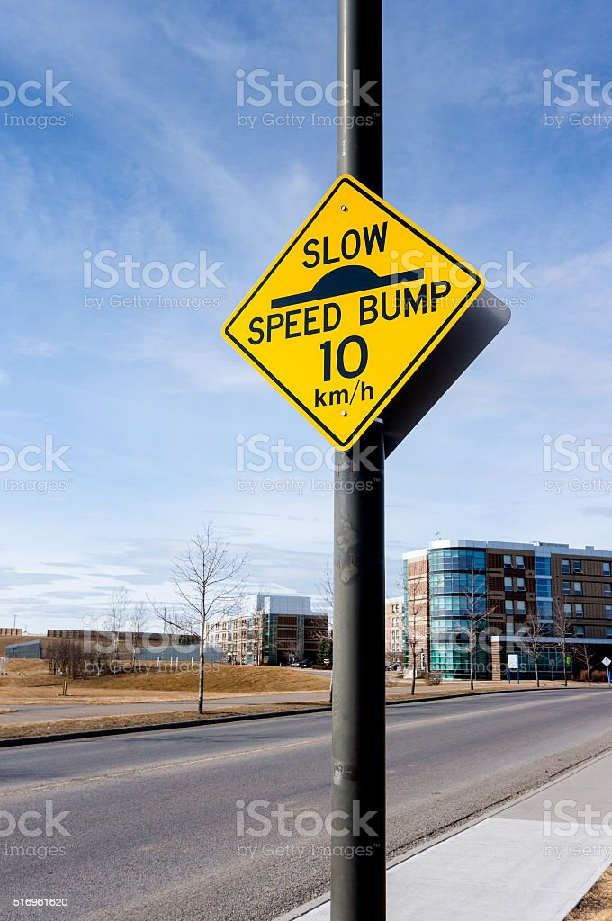 Slow Speed Bump Road Sign on Residential Street stock photo