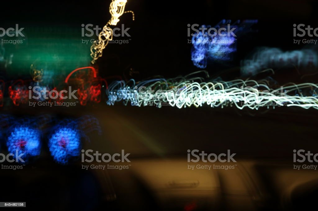 Slow speed shutter of abstract colorful light's motion in speeding car on dark blurred background. stock photo