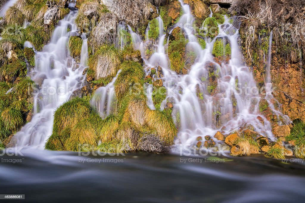 Slow water of a spring glides over rocks stock photo