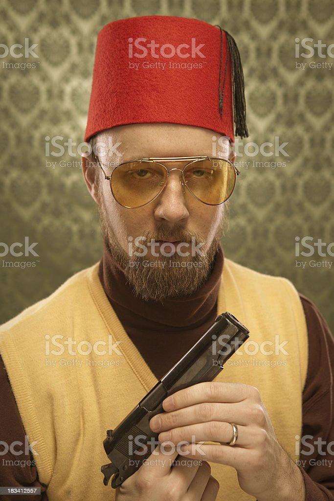 Sly stoic assasin Egyptian man holdng 9mm gun & glasses royalty-free stock photo