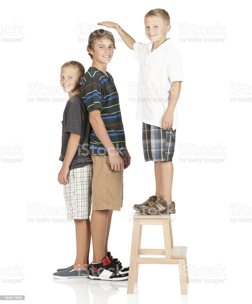 Smal boy standing on stool and comparing height stock photo