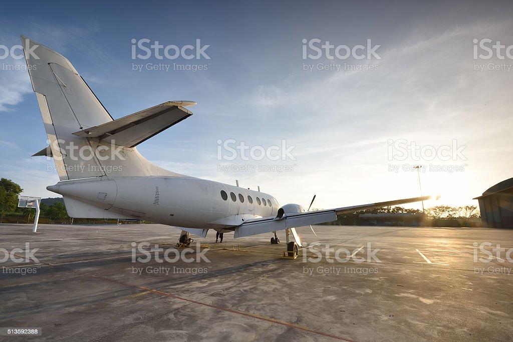 Small aeroplane infront of aircraft hangar during sunrise stock photo