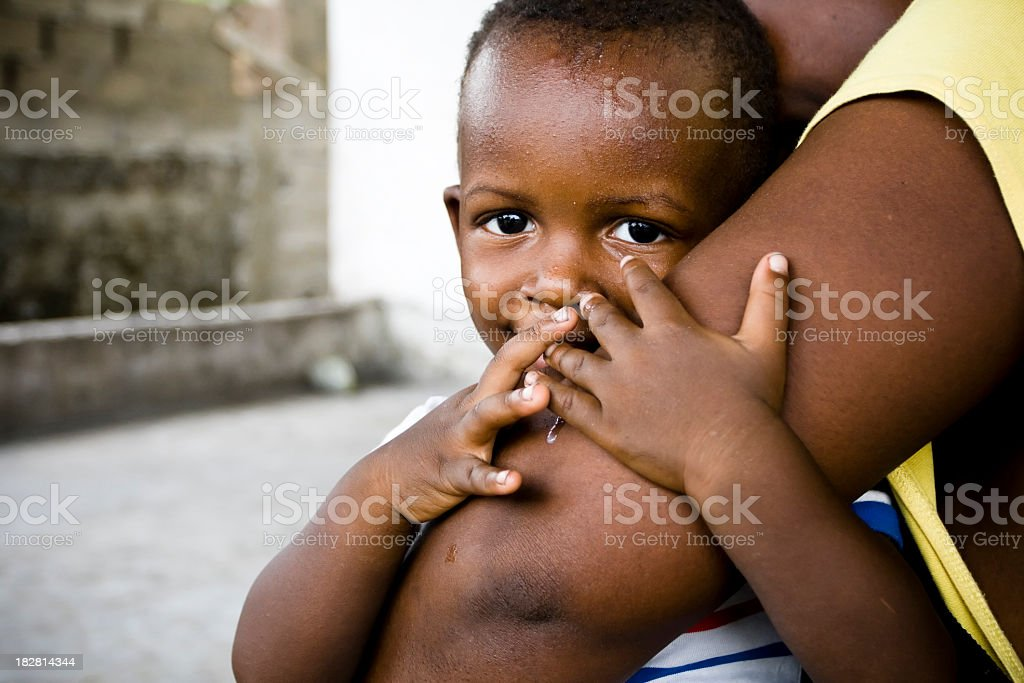 Small African baby boy embracing his mothers comforting arm stock photo