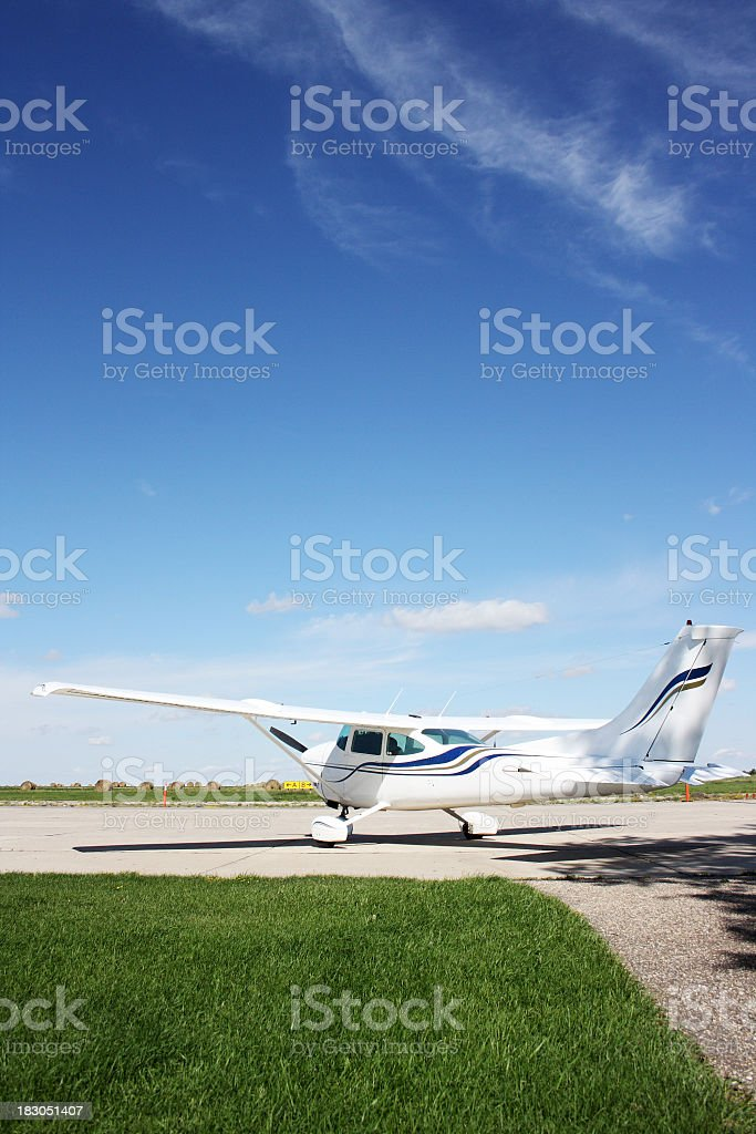 Small airplane on a dirt airstrip against a blue sky stock photo