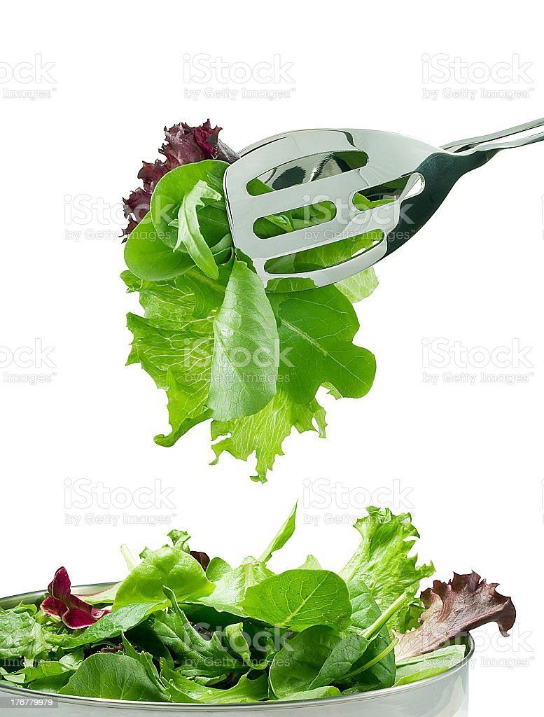 A small amount of salad leaves being picked out of a bowl stock photo