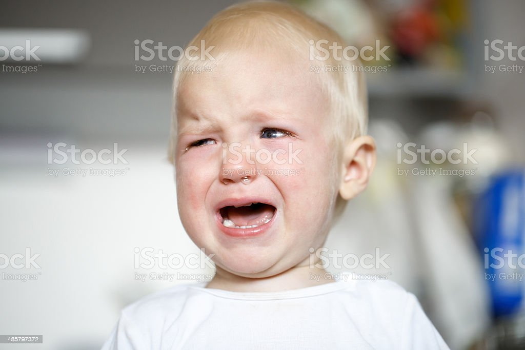 Small and sick crying toddler in pain stock photo
