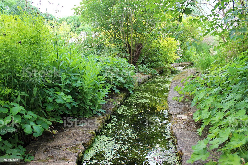 Small artificial stream leading to waterfall / pond, water gardens image stock photo