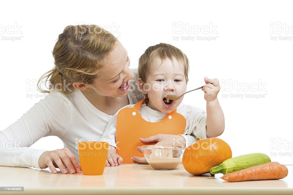 small baby boy eating vegetable puree by spoon stock photo
