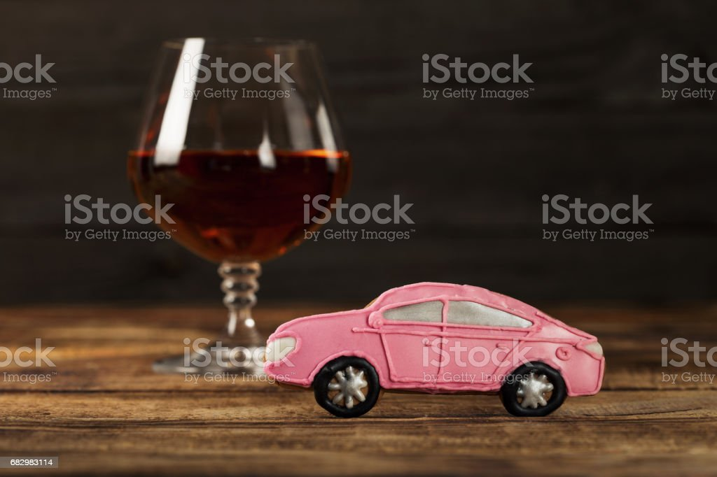 Small baby car with a glass of brandy on a wooden table stock photo
