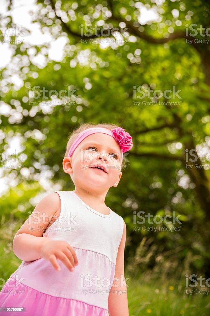 Small baby girl dressed in pink outdoors royalty-free stock photo