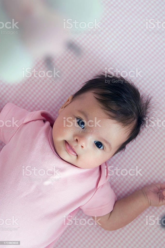A small baby in a crib with a mobile, wearing a pink onesie royalty-free stock photo