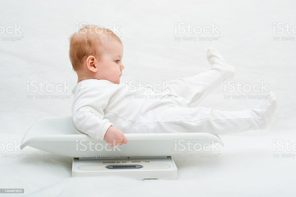 A small baby in a white onesie sitting in a baby sized scale stock photo