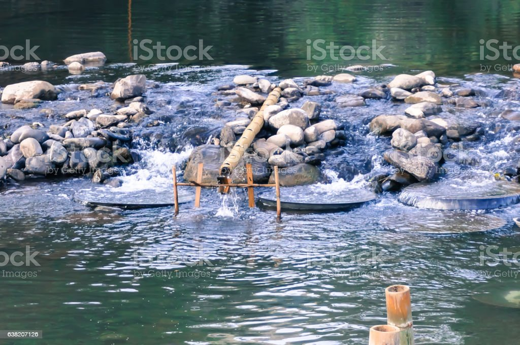 Small bamboo turbine and man made stone weiracross the river. stock photo