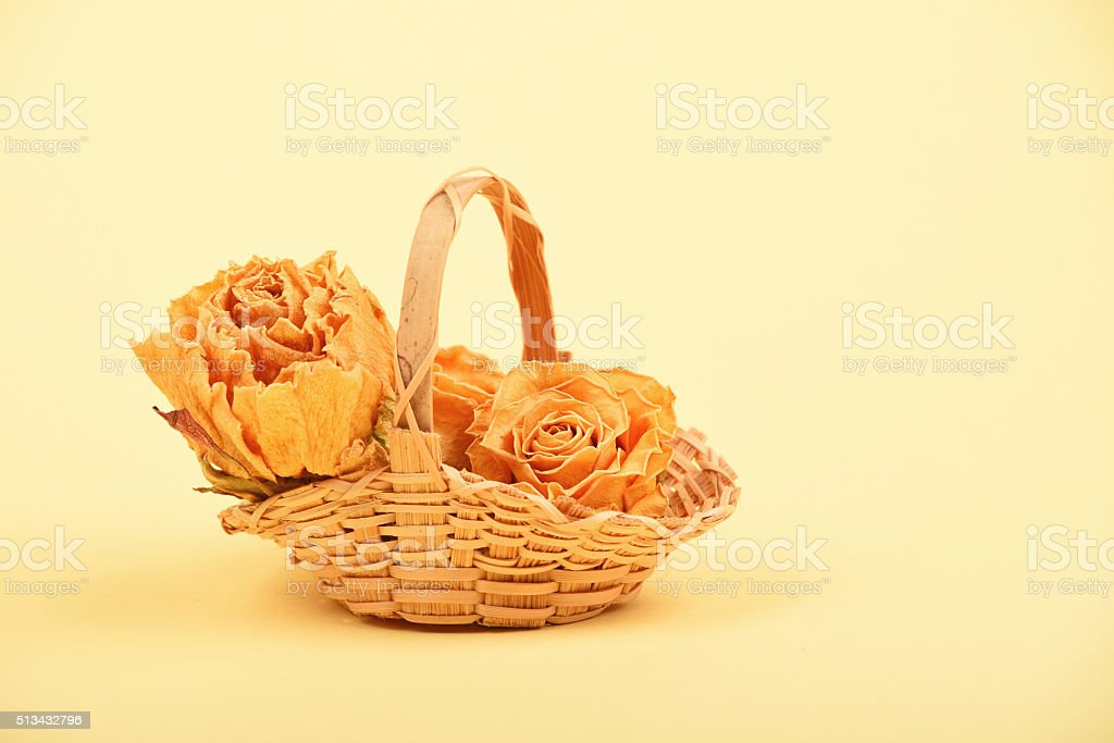 Small basket of dried roses on beige paper royalty-free stock photo