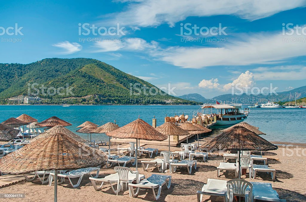 small beach with umbrellas and sunbeds stock photo