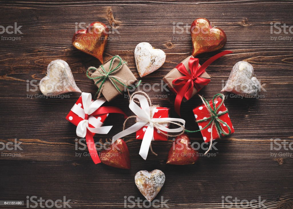 Small beautifully wrapped gifts and hearts in the shape of a heart on a wooden background stock photo