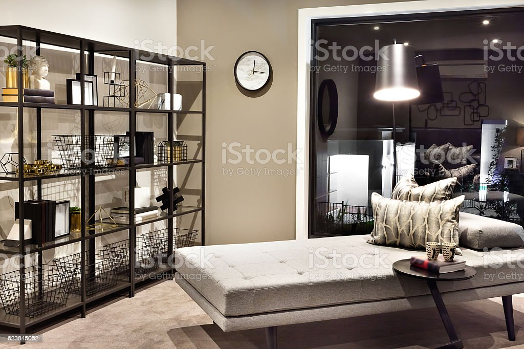 Small bed and pillows beside a shelf with fancy items stock photo