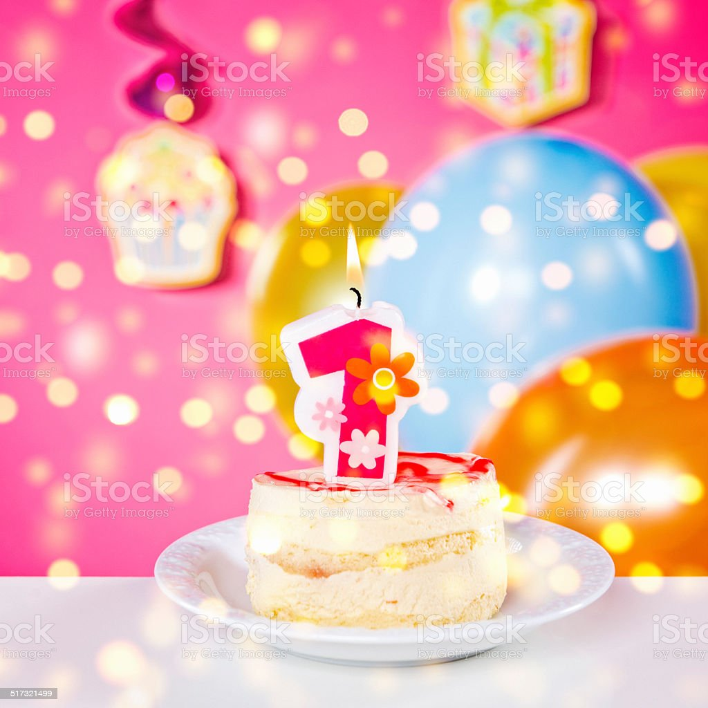 Small birthday cake with number one burning candle, pink background stock photo